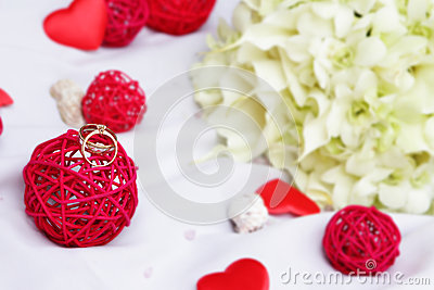 Wedding rings, decoration and bridal bouquet over white