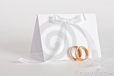 Wedding rings and invite with white bow