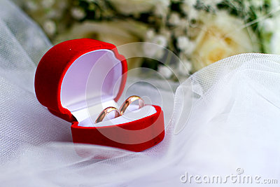 Wedding rings in a red box and a bouquet close-up