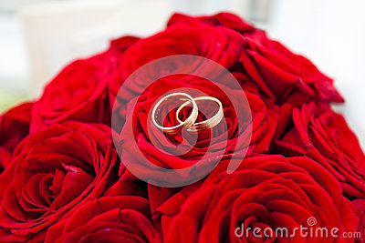 Wedding rings on red roses