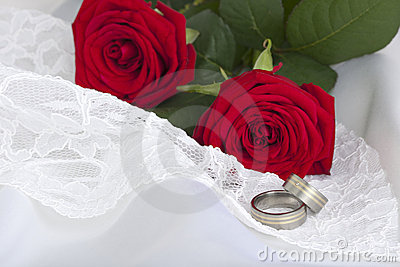 Wedding rings and red roses on white lace and silk