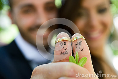 Wedding rings on their fingers painted with the bride and groom Stock Photo