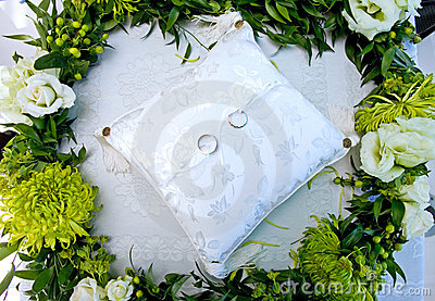 Wedding rings on a white cushion in a wreath of flowers