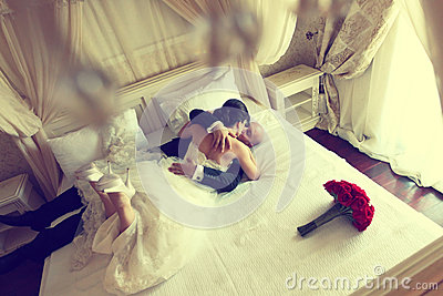 Wedding shot of bride and groom lying in a stylish white bed red flower bouquet