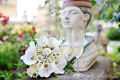 Wedding white roses bouquet near champagne glasses