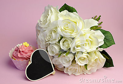 Wedding white roses bouquet with pink cupcake and blank heart sign.