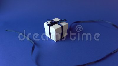 Weißes Geschenkkarton mit klassisch blauem Band auf blauer Oberfläche Oberansicht stock footage