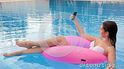 Weiblich macht Foto auf Android und Schwimmen auf aufblasbarem Ring im Schwimmbad stock video
