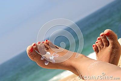 Weibliche Füße auf dem Strand