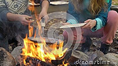 Weibliche Freunde kochen traditionelle Pfannkuchen über einem offenen Feuer im Camp bei einer Wanderung im Freien stock footage