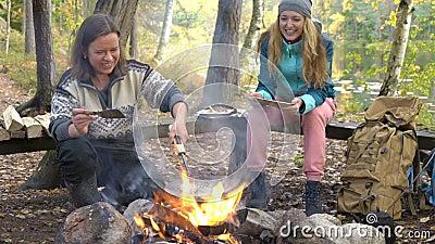 Weibliche Freunde kochen traditionelle Pfannkuchen über einem offenen Feuer im Camp bei einer Wanderung im Freien stock video footage
