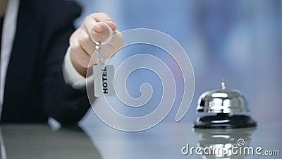 Weibliche Hand, die bei Empfang Hotelzimmerschlüssel nahe Glocke, Gastfreundschaftsdienstleistungen hält stock video