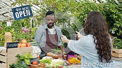 Weibliche Kunden kaufen Gemüse und Brot aus ökologischem Landbau auf dem Agrarmarkt stock footage
