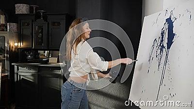 Weibliche Maler, die blaue Acrylfarbe mit einer Pinsel auf weißen Leinwand spritzen Schwungbewegung Pinselüberspritzen flüssiger  stock footage