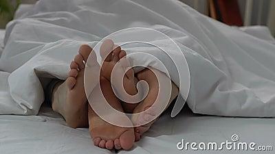 Weibliche und männliche Beine im Bett, glückliches Paar, das Liebe am Morgen, Nahaufnahme macht stock footage