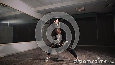 Weiblicher Tänzer im weißen Hemd, in der schwarzen Hose und schwarzen in der Kappe, die Jazz modernes Tanzen zeigt Mädchen tanzt