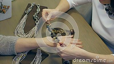 Weiblicher Verkäufer hilft eleganter Frau, ein teures Armband an zu versuchen stock video footage