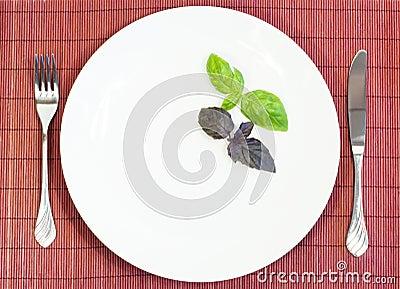 Weiße Platte mit Gabel und Messer