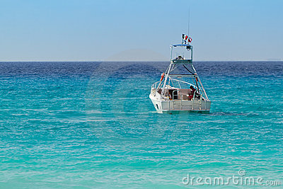 Weißes Boot auf turquise karibischem Meer