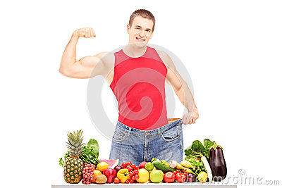 Weight loss man showing his muscles and standing behind a pile o