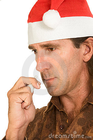 Weihnachtsgrippe - mittlerer gealterter Mann, der nasalen Spray verwendet