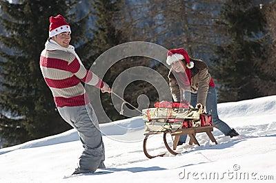 Weihnachtspaare, die mit Geschenken im Schnee spielen