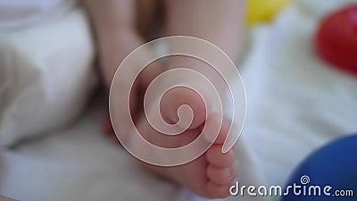 Weinig baby in luiersspelen met voet Ontwikkeling van kinderen van peuterleeftijd Close-up stock footage