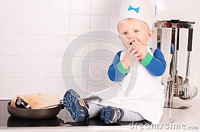 Weinig babychef-kok in de kokhoed die pannekoeken maakt