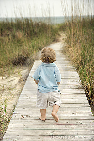 Weinig jongen die onderaan strandgang loopt.