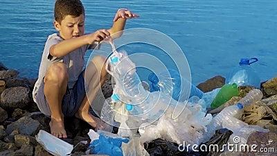 Weinig kindvrijwilliger die het strand schoonmaken bij de oceaan Veilig ecologieconcept stock video