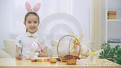 Weinig leuk en aanbiddelijk meisje glimlacht en speelt met Paashazen in haar handen De vakantie van conceptenpasen