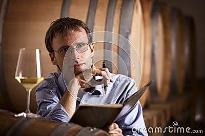Weinproduzent, der im Keller erwägt.