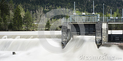 Weir plant with flowing water and trees in backgro