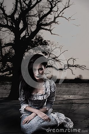 Weird female witch on background with dead tree