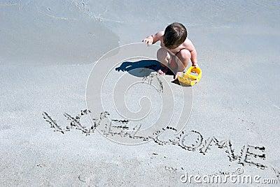 Welcome written in a sandy beach