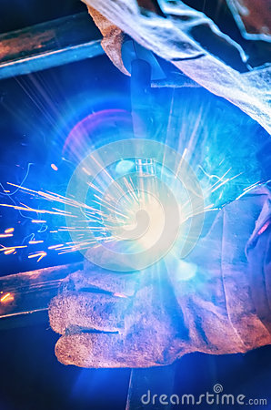 Free Welder In A Protective Mask In A Dark Shop Floor Weld Metal Parts. By Welding Sparks Fly In Different Directions Royalty Free Stock Image - 85927546