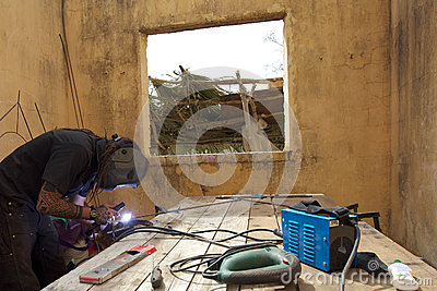 Welder at work in old house in Africa