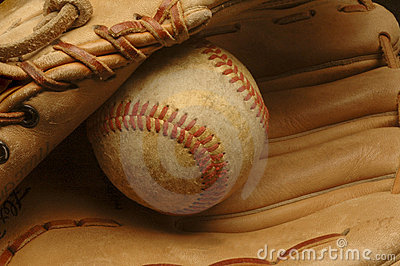 Well-used baseball nestled in a glove.