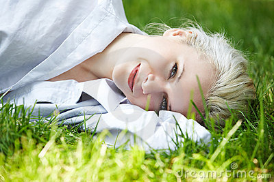 Wellbeing. Happy smiling woman has rest on grass