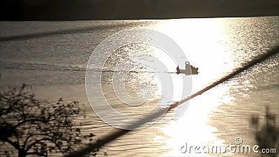 Wenig Fischerboot durch dämmernde Sonnenreflexion stock video