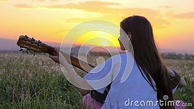Wenig Jugendlichmädchen, welches die Gitarre spielt Schöne Sommerlandschaft bei Sonnenuntergang Kunst Musik-Konzepte Löwenzahnfel stock video