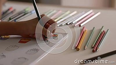 Wenig M?dchen f?rbt Bilder in einem Buch mit farbigem Bleistift stock video footage