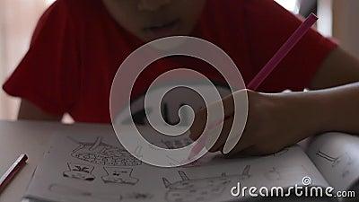 Wenig M?dchen f?rbt Bilder in einem Buch mit farbigem Bleistift stock footage