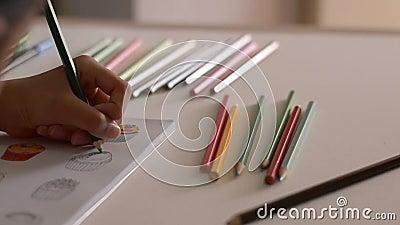 Wenig M?dchen f?rbt Bilder in einem Buch mit farbigem Bleistift stock video