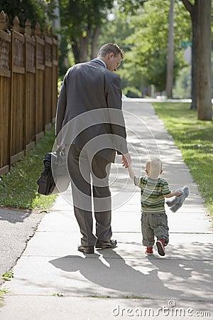 Werkende Papa die met zoon loopt