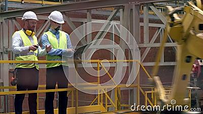 Werknemers in de fabriek Mannelijke werknemers controleren machines tijdens het lopen in een faciliteit stock videobeelden