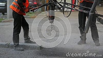 Werknemers repareren kleine stukjes door asfaltspaanders op de weg te spuiten stock footage