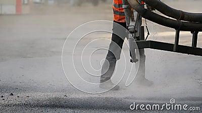Werknemers repareren kleine stukjes door asfaltspaanders op de weg te spuiten stock video