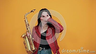 Wesoła młoda kobieta w ładnych ubraniach trzymająca usta otwarte, przykrywająca oczy ręką zdjęcie wideo