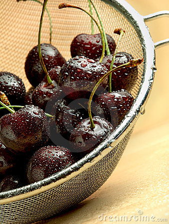 Wet dark cherries in mesh sieve on wooden table